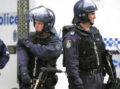 Riot police watch demonstrators in Sydney.