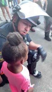 Poliziotto conforta bambina in lacrime durante manifestazione-min